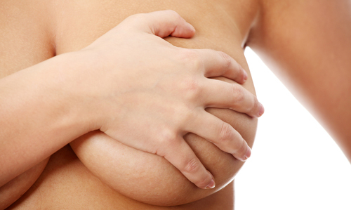 Young caucasian adult woman examining her breast